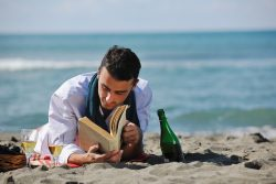 man reading book at beach