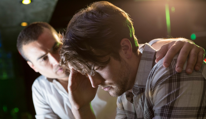 Man comforting his depressed friend